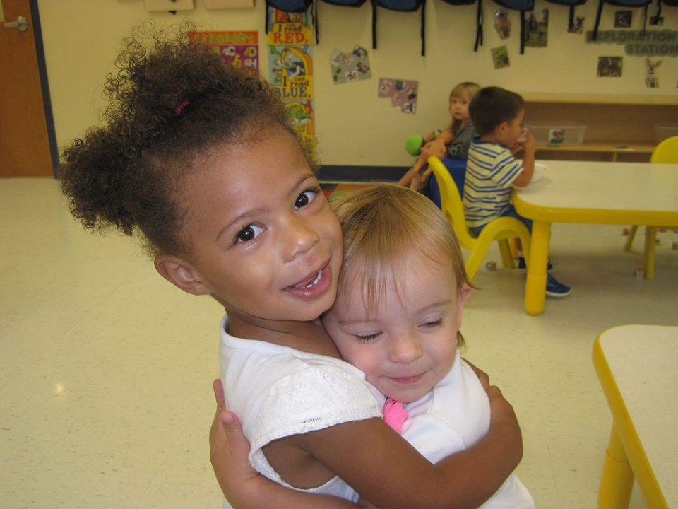 Diverse toddlers hugging each other, showing love and care, at a Preschool & Daycare/Childcare Center serving Apex & Fuquay-Varina, NC