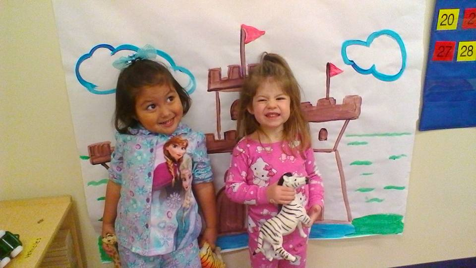 Cute little preschool girls very happy wearing cute design Frozen and Hello Kitty pajamas , holding Zebra and Tiger stuff toy, with Castle painted background, at a Preschool & Daycare/Childcare Center serving Apex & Fuquay-Varina, NC