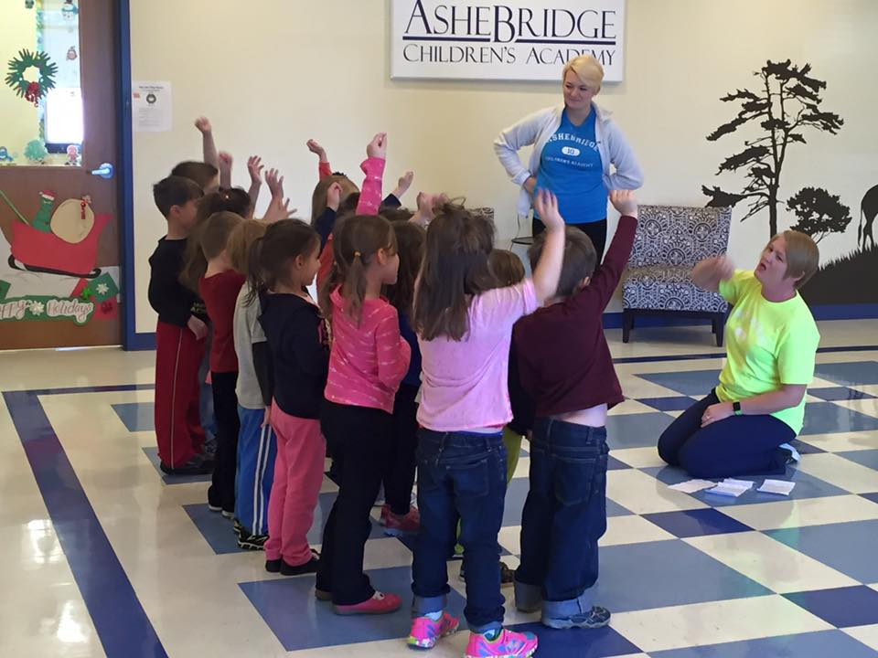 Children raising hands, to answer teachers question, at a Preschool & Daycare/Childcare Center serving Apex & Fuquay-Varina, NC