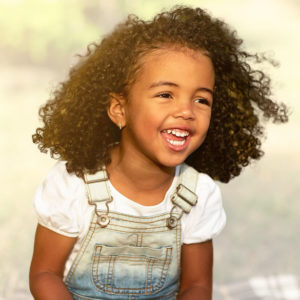 Happy african-american girl sitting on blanket and laughing, walking in park, at a Preschool & Daycare/Childcare Center serving Apex & Fuquay-Varina, NC