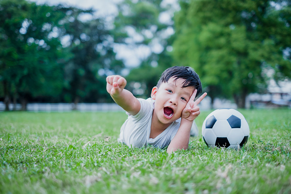 Little Asian child playing football and celebrating on grass. at a Preschool & Daycare/Childcare Center serving Apex & Fuquay-Varina, NC