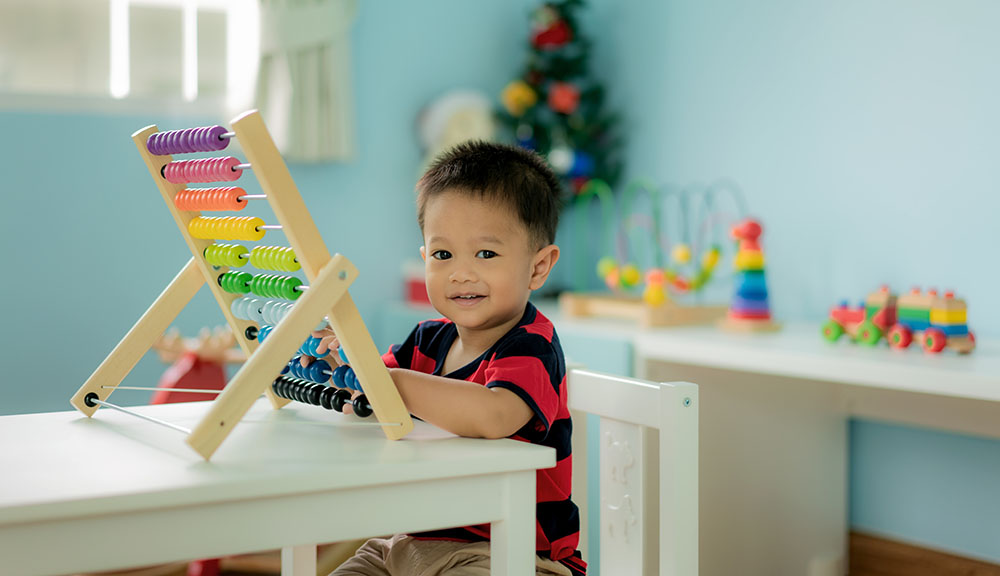Asian Toddler baby boy learns to count. Cute child playing with abacus toy. Little boy having fun indoors at home. Educational concept for Toddler baby at a Preschool & Daycare/Childcare Center serving Apex & Fuquay-Varina, NC