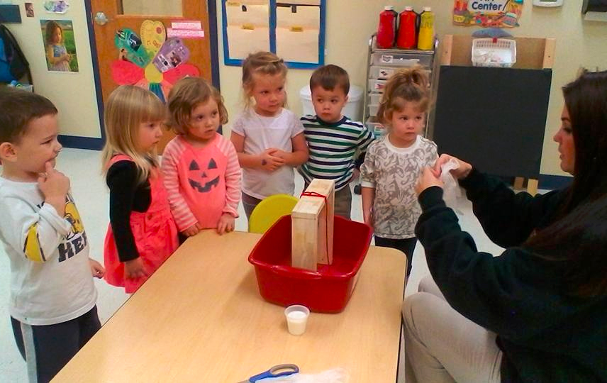 Teacher giving instructions to young little preschool kids on their school activity at a Preschool & Daycare/Childcare Center serving Apex & Fuquay-Varina, NC