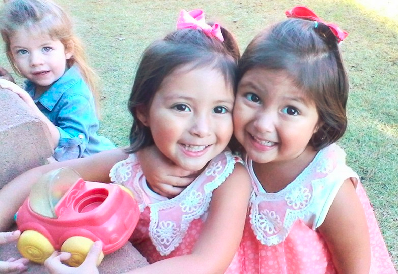 Happy cute little twin girls enjoying each others company playing Happy young little girls working with art project at a Preschool & Daycare/Childcare Center serving Apex & Fuquay-Varina, NC