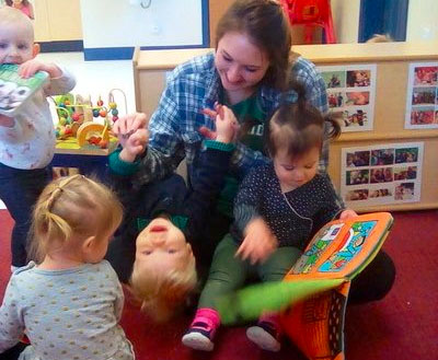 toddlers enjoy playing and reading books with teacher at a Preschool & Daycare/Childcare Center serving Apex & Fuquay-Varina, NC