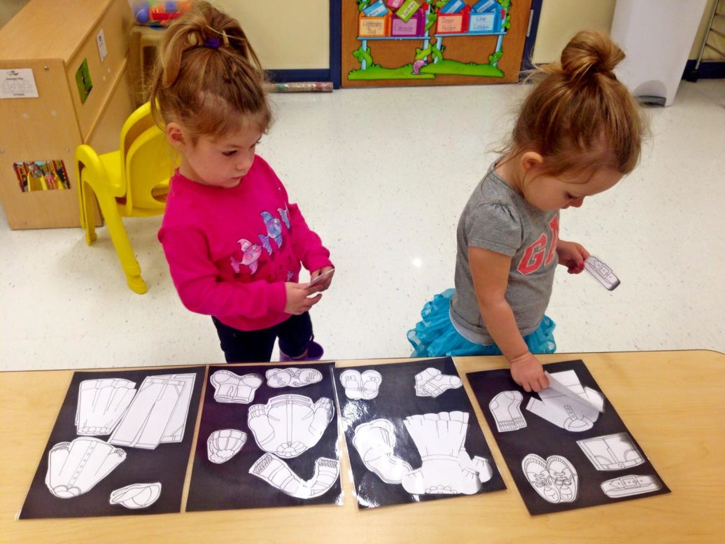 Cute little young girls enjoying playing cutouts of dress and shoes at a Preschool & Daycare/Childcare Center serving Apex & Fuquay-Varina, NC