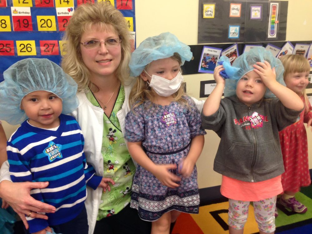 Little young kids wearing protective mask and hair net with teacher at a Preschool & Daycare/Childcare Center serving Apex & Fuquay-Varina, NC