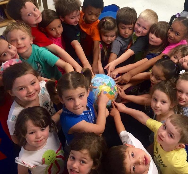 Children gathering around touching the globe in the middle at a Preschool & Daycare/Childcare Center serving Apex & Fuquay-Varina, NC