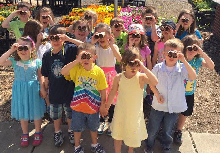 Group of preschool kids on an improvised binoculars at a Preschool & Daycare/Childcare Center serving Apex & Fuquay-Varina, NC