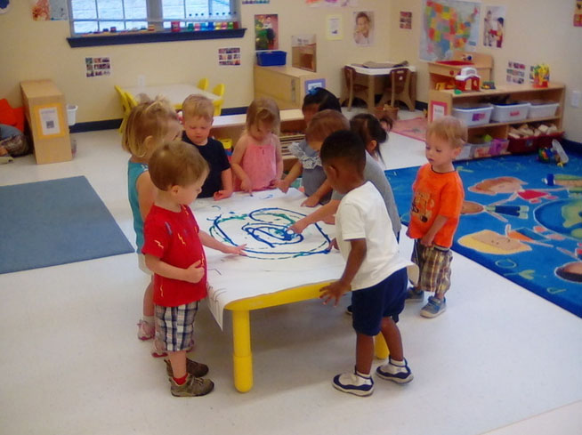 Group of toddlers doing hand painting on the table at a Preschool & Daycare/Childcare Center serving Apex & Fuquay-Varina, NC