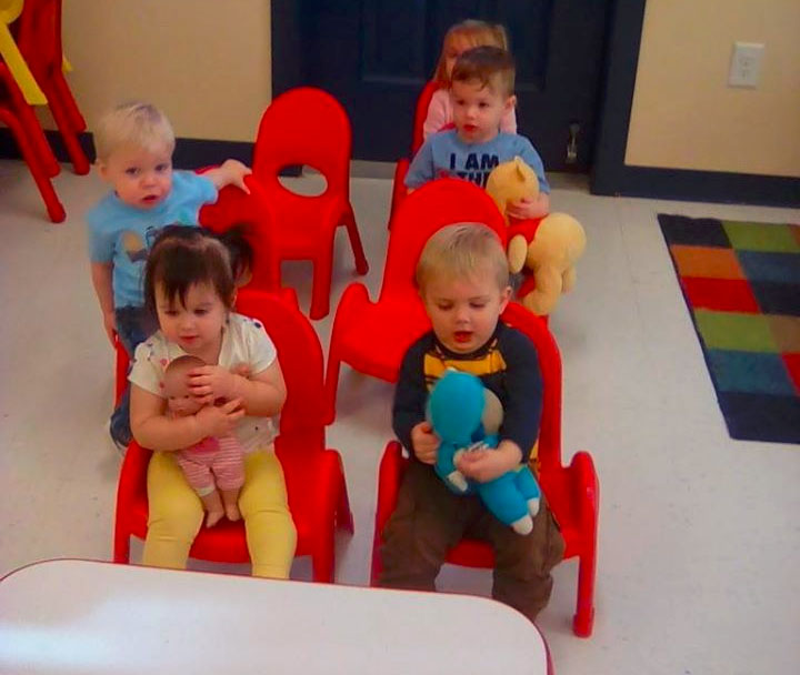Group of toddlers with stuff toys on their lap while sitting on red small chairs at a Preschool & Daycare/Childcare Center serving Apex & Fuquay-Varina, NC