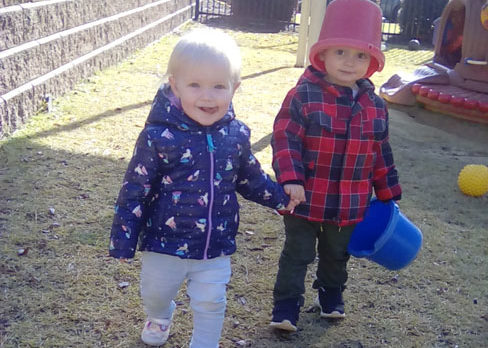 Young little boys holding each others hands one holding a plastic bucket with a bucket on his head at a Preschool & Daycare/Childcare Center serving Apex & Fuquay-Varina, NC
