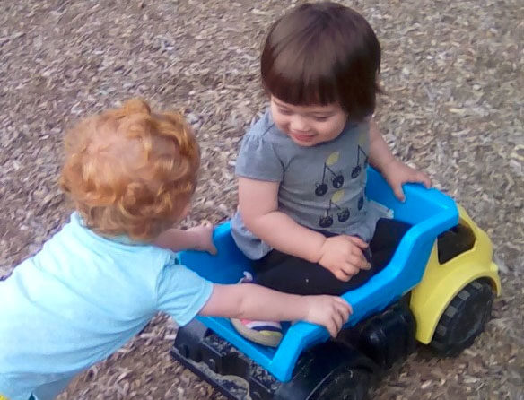 Young little boys playing on the back of a toy truck at a Preschool & Daycare/Childcare Center serving Apex & Fuquay-Varina, NC