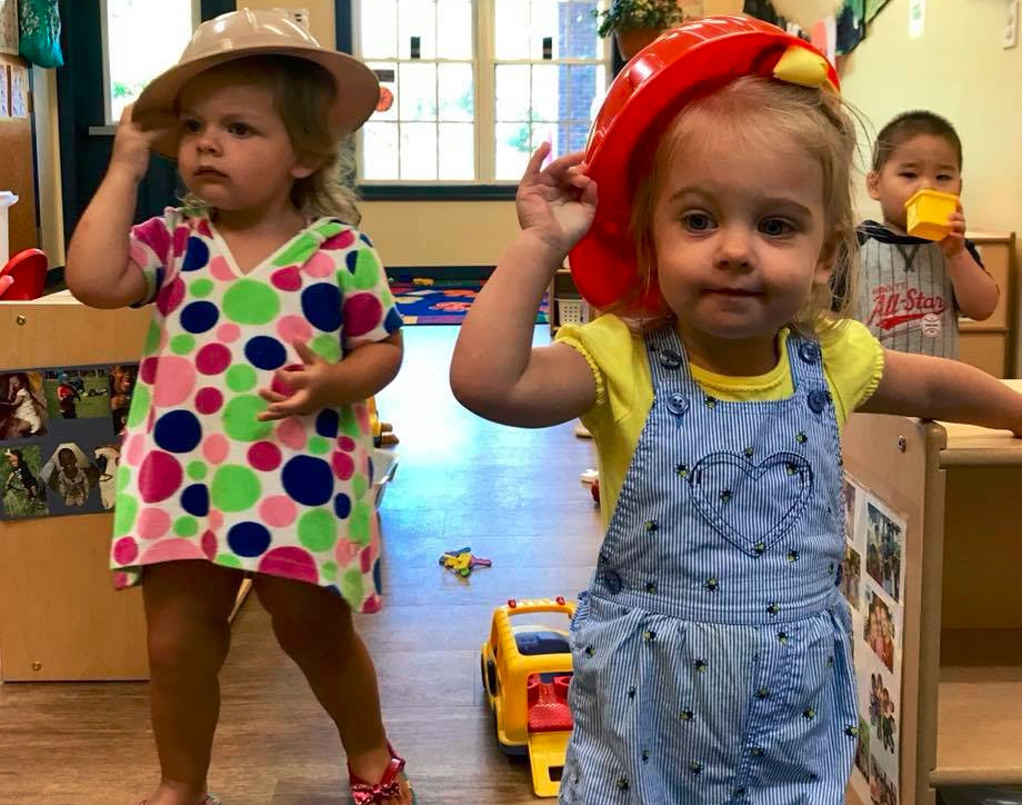 Two adorable young preschoolers wearing hat at a Preschool & Daycare/Childcare Center serving Apex & Fuquay-Varina, NC