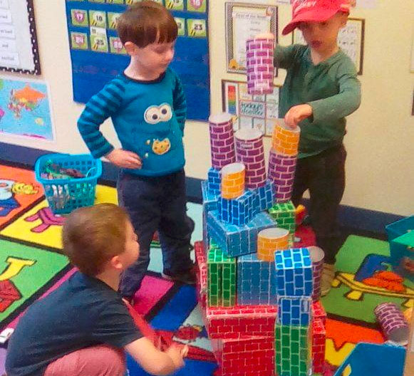 Little kids playing with colorful brick design cut out boxes and stacking them to create a castle at a Preschool & Daycare/Childcare Center serving Apex & Fuquay-Varina, NC