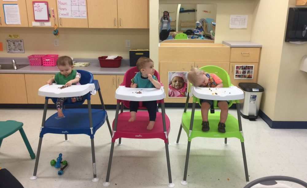 Cute little toddlers while on the baby chair eating at a Preschool & Daycare/Childcare Center serving Apex & Fuquay-Varina, NC