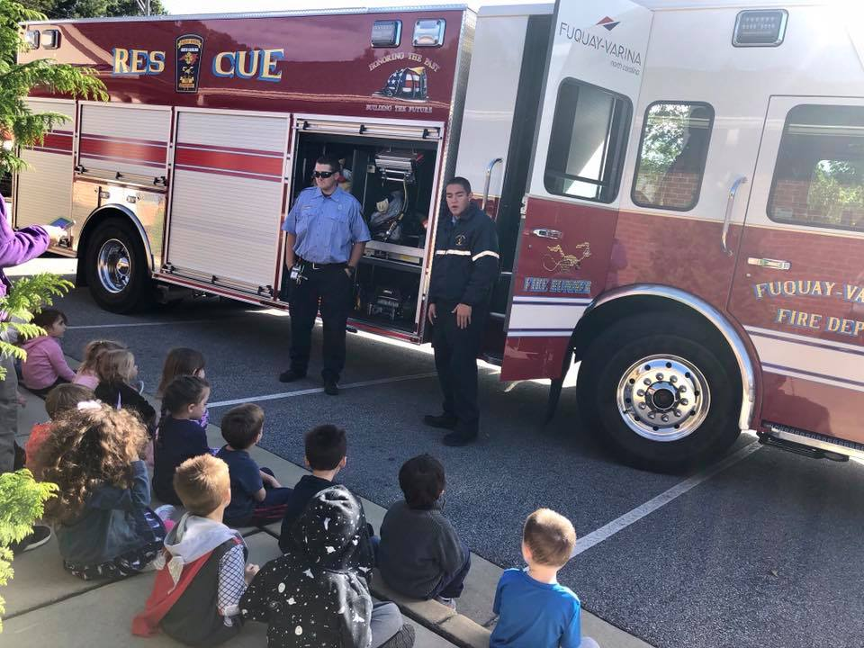 in house visits community, Firefighters in front of children teaching them at a Preschool & Daycare/Childcare Center serving Apex & Fuquay-Varina, NC