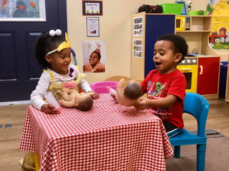 African American little young kids playing with baby dolls at a Preschool & Daycare/Childcare Center serving Apex & Fuquay-Varina, NC