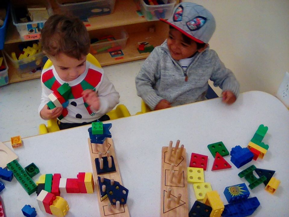 Toddler boys enjoy playing colorful educational building blocks at a Preschool & Daycare/Childcare Center serving Apex & Fuquay-Varina, NC