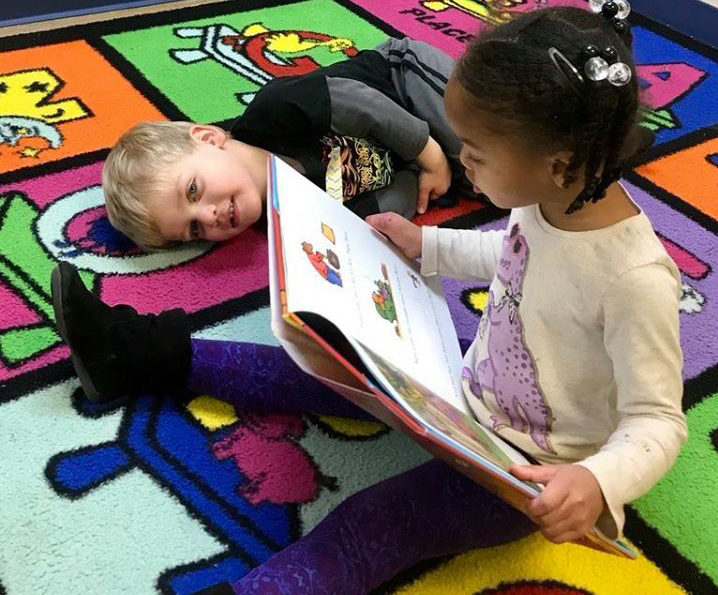 Preschool kid girl reading a some education story book while another kid boy is lying beside her