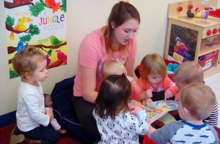 Beautiful teacher reading a story book to cute little toddlers at a Preschool & Daycare/Childcare Center serving Apex & Fuquay-Varina, NC