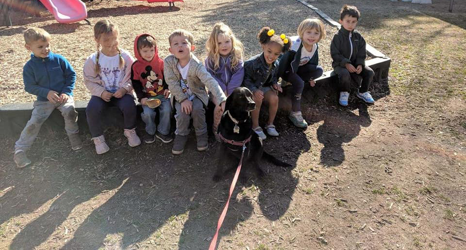 Children sitting with a dog in the middle at a Preschool & Daycare/Childcare Center serving Apex & Fuquay-Varina, NC