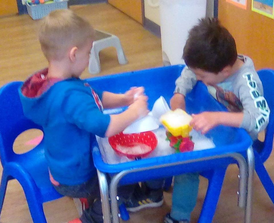 Young little boys playing with ice on a blue plastic container at a Preschool & Daycare/Childcare Center serving Apex & Fuquay-Varina, NC