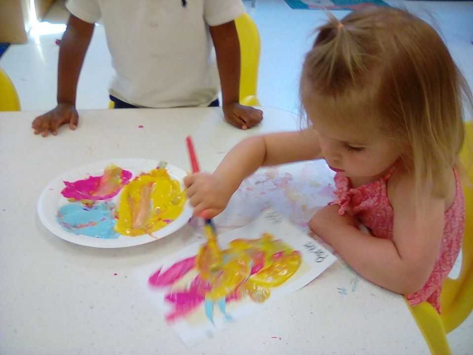 little preschool girl holding a brush and doing a painting on a piece of paper at a Preschool & Daycare/Childcare Center serving Apex & Fuquay-Varina, NC