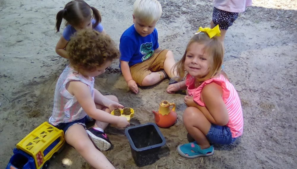 group of preschool kids playing sand at a Preschool & Daycare/Childcare Center serving Apex & Fuquay-Varina, NC