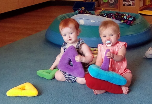 Adorable toddlers playing with colorful triangle shaped pillow at a Preschool & Daycare/Childcare Center serving Apex & Fuquay-Varina, NC