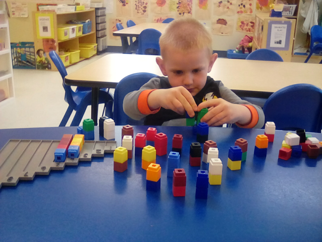 Kid boy playing with educational building blocks at a Preschool & Daycare/Childcare Center serving Apex & Fuquay-Varina, NC