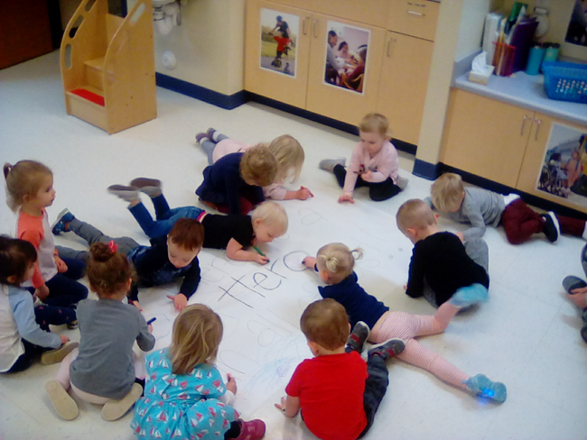 Group of toddler doing educational activity writing on a huge piece of paper on the floor at a Preschool & Daycare/Childcare Center serving Apex & Fuquay-Varina, NC