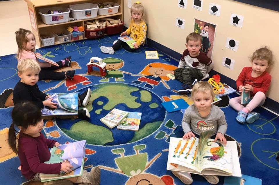 Children reading storybooks, developmental activity, at a Preschool & Daycare/Childcare Center serving Apex & Fuquay-Varina, NC