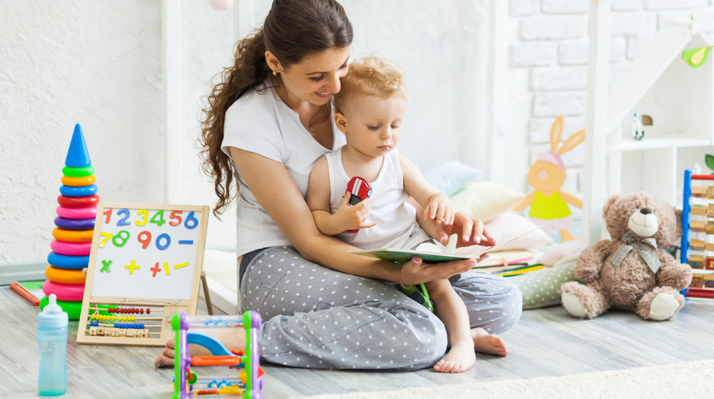 Mother with child playing educational toys and reading book in the room at a Preschool & Daycare/Childcare Center serving Apex & Fuquay-Varina, NC