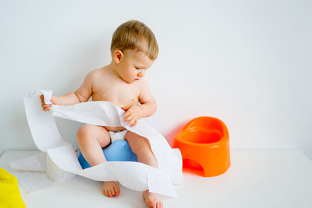 Cute baby sitting on the potty at a Preschool & Daycare/Childcare Center serving Apex & Fuquay-Varina, NC