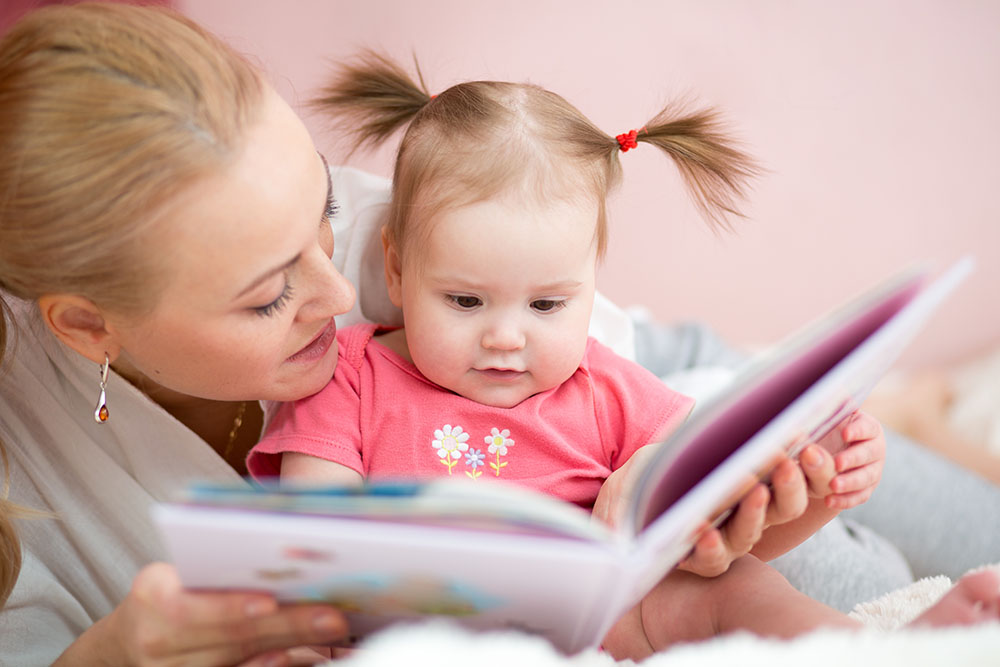 Mommy reads her baby daughter a book at a Preschool & Daycare/Childcare Center serving Apex & Fuquay-Varina, NC