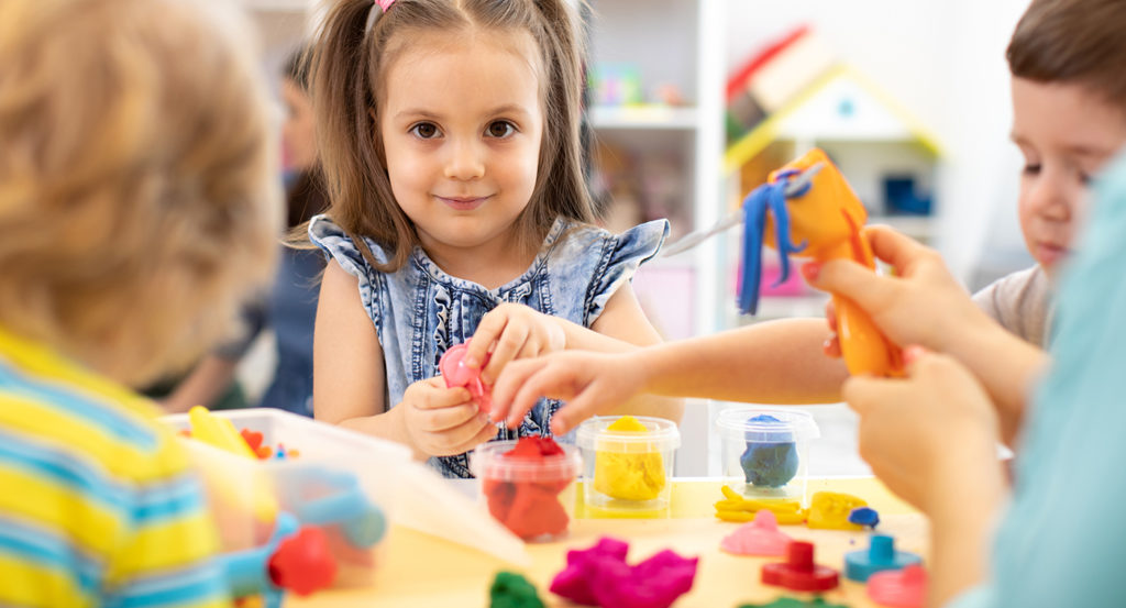 Group of kids playing with modeling clay in nursery at a Preschool & Daycare/Childcare Center serving Apex & Fuquay-Varina, NC