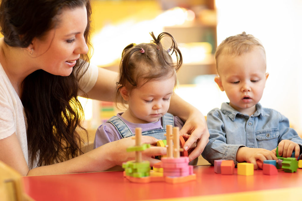 Children with teacher play with shapes and colorful wooden puzzle in a classroom at a Preschool & Daycare/Childcare Center serving Apex & Fuquay-Varina, NC