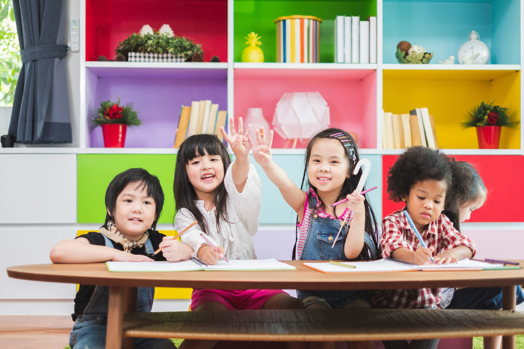 Group diverse kids studying at school, rising hands for answer and question in classroom, kids education concept at a Preschool & Daycare/Childcare Center serving Apex & Fuquay-Varina, NC