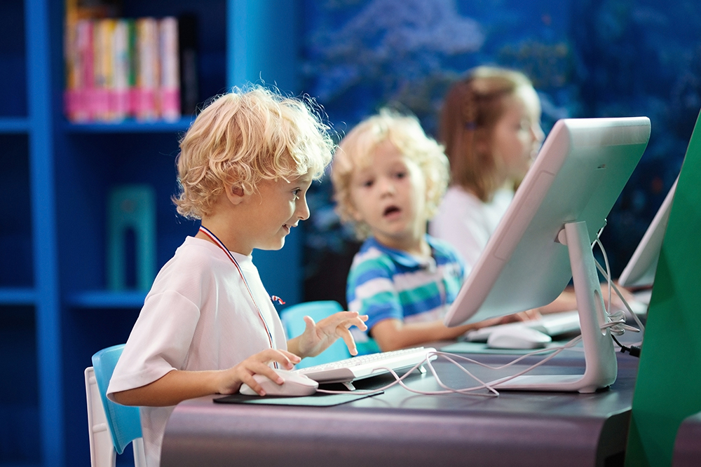 Kids with computer. Children learning and studying information and communications technology using personal computers in school class or library. Student at Pc. Modern education device for child at a Preschool & Daycare/Childcare Center serving Apex & Fuquay-Varina, NC