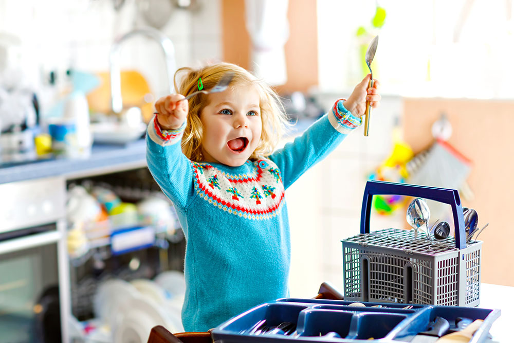 Cute little toddler girl helping in the kitchen with dish washing machine. Happy healthy blonde child sorting knives, forks, spoons, cutlery. Baby having fun with helping housework mother and father at a Preschool & Daycare/Childcare Center serving Apex & Fuquay-Varina, NC
