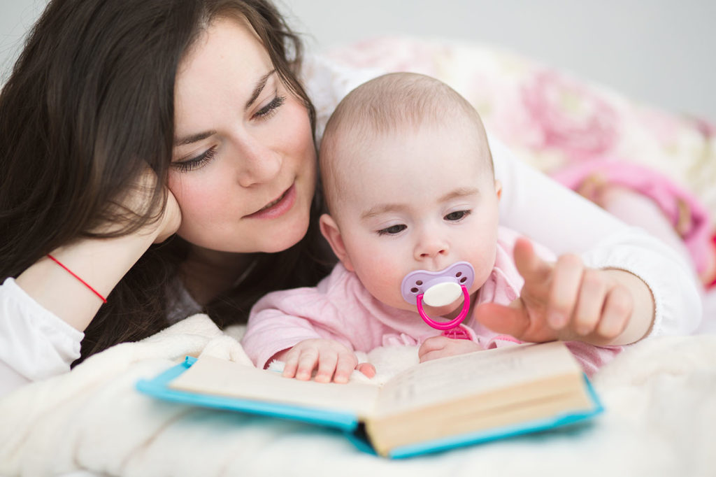Young mother with her little daughter reading book at a Preschool & Daycare/Childcare Center serving Apex & Fuquay-Varina, NC