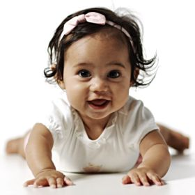 Cute little baby girl smiling while crawling, baby photo shoot concept, at a Preschool & Daycare/Childcare Center serving Apex & Fuquay-Varina, NC