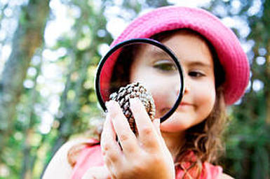 Young little preschool girl using a magnifying glass trying to check a shell at a Preschool & Daycare/Childcare Center serving Apex & Fuquay-Varina, NC