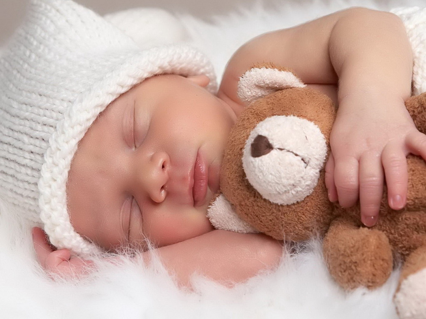 Cute sleeping baby hugging a teddy bear at a Preschool & Daycare/Childcare Center serving Apex & Fuquay-Varina, NC
