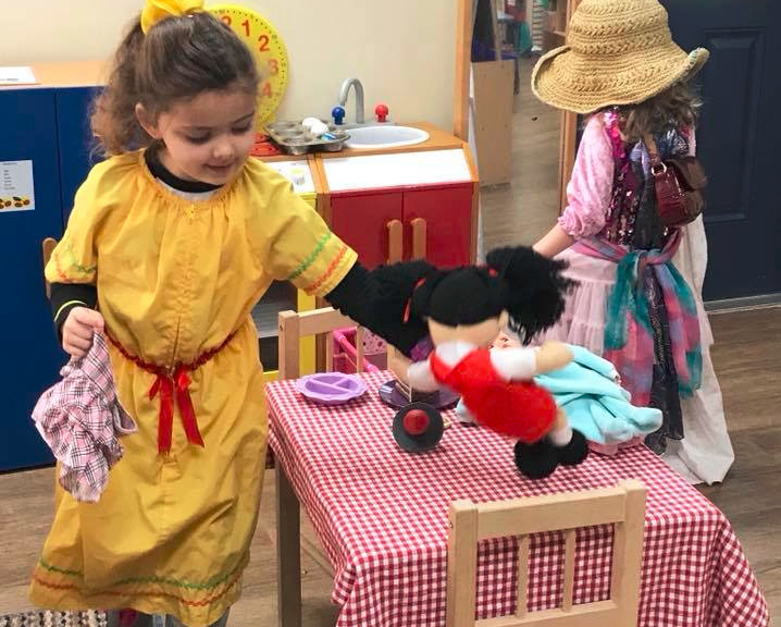 Little kid girls in costume while playing with doll at a Preschool & Daycare/Childcare Center serving Apex & Fuquay-Varina, NC
