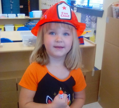 Happy young little preschool girl wearing a firefighter hat at a Preschool & Daycare/Childcare Center serving Apex & Fuquay-Varina, NC