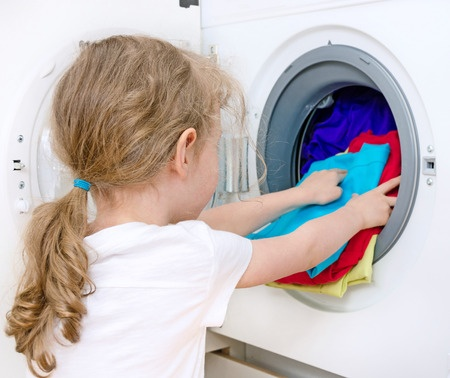 Young little girl putting some laundry in a washing machine at a Preschool & Daycare/Childcare Center serving Apex & Fuquay-Varina, NC