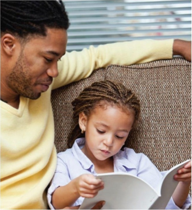 African american dad and young little daughter reading an educational book at a Preschool & Daycare/Childcare Center serving Apex & Fuquay-Varina, NC