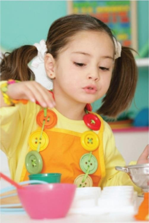 Beautiful little young girl on a ponytail wearing colorful shirt playing with educational toys at a Preschool & Daycare/Childcare Center serving Apex & Fuquay-Varina, NC